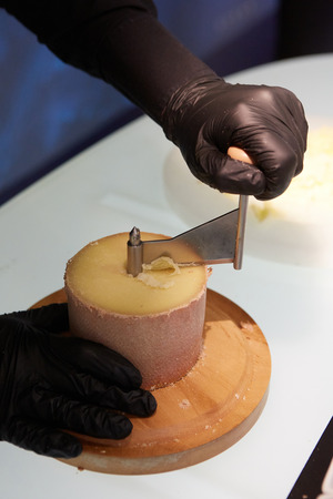 Special cheese knives. The girolle scraper. Making cheese shaving on girolle, closeup