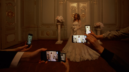 Guests take photographs of the bride on smartphones. Focus on smartphones. Stock fotó