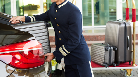Bellboy taking baggage of guest from thee car to his room Stock Photo