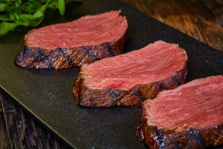 Sous-vide steak cut into pieces, cooked to eat beef on the stone table Stock Photo