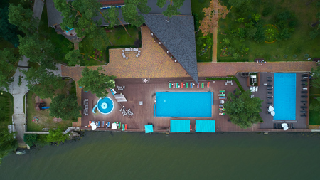 Aerial view of luxury house garden with swimming pool surrounded by trees.