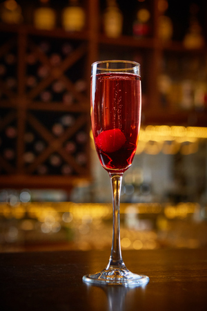 Red Cocktail in Champagne Glass near in the Bar with Amazing Blurred Background. Stock fotó