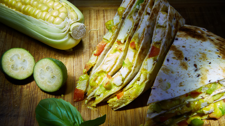 Mexican quesadilla with chicken, cheese and peppers on wooden table