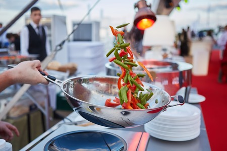 chef tossing vegetables in a wok in an outdoor kitchen.