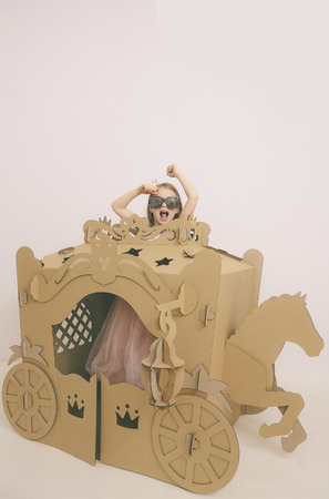 Cute Little Caucasian Girl in Pastel Pink Dress Princess Preparing for Birthday Party and posing in fairy tale carriage. Фото со стока