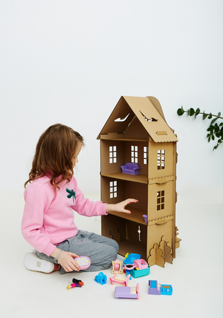 Happy girl plays with cardboard doll house. Funny lovely child is having fun.