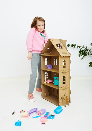 Happy girl plays with doll house and doll house furniture. Funny lovely child is having fun.