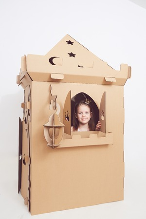 Little princess in crown play with her cardboard castle. True emotion of happiness of the child.