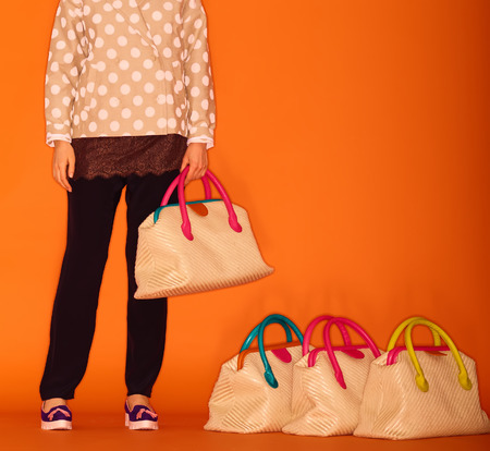 Woman choosing the bag from many bags.Isolated on green background. Shopping addiction