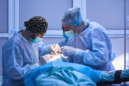 Surgical team performing surgery in modern operation theater,Team of doctors concentrating on a patient during a surgery,Team of doctors working together during a surgery in operating room