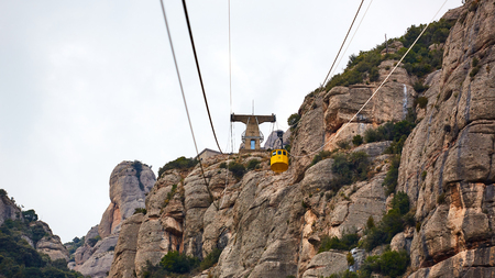 Yellow cable car in the Aeri de Montserrat rise to de Montserrat Abbey near Barcelona, Spain, Catalonia.