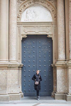 Montserrat, Spain - April 5, 2019: Young wonan poses in front of the Santa Maria de Montserrat Abbey, Catalonia, Spain.