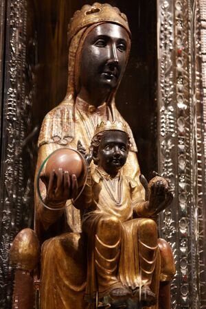 Montserrat, Spain - April 5, 2019: 12th century statue of Black Madonna of Montserrat in cathedral of Montserrat Monastery. She is protected glass cover with orb protruding for pilgrims to touch. Barcelona Province Catalonia Spain.