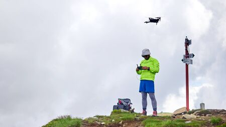 Guy tourist launches quadrocopter in the mountains