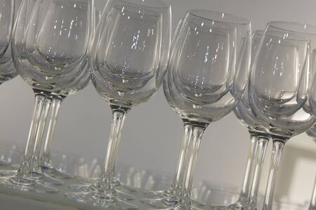 Welcome drink. Rows of empty wine or champagne glasses close up. glass goblets on the white table. Empty crystal wineglass. glass goblet on a high leg. Restaraunt bar concept.