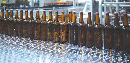 Botellas de cerveza en la cinta transportadora. Kelvin superficial. Enfoque selectivo.