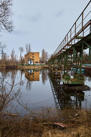 The abandoned river port in Pripyat. Abandoned ships in the river near of Chernobyl. Modern ruins. Radioactive metal