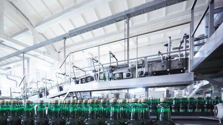 Bottiglie di plastica per birra o bevanda gassata in movimento su nastro trasportatore. DOF poco profondo. Messa a fuoco selettiva.