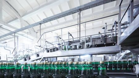 Bouteilles en plastique pour bière ou boisson gazeuse se déplaçant sur convoyeur. DOF peu profond. Mise au point sélective.