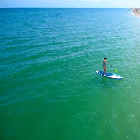 Aerial drone birds eye view of young woman exercising sup board in turquoise tropical clear waters Imagens