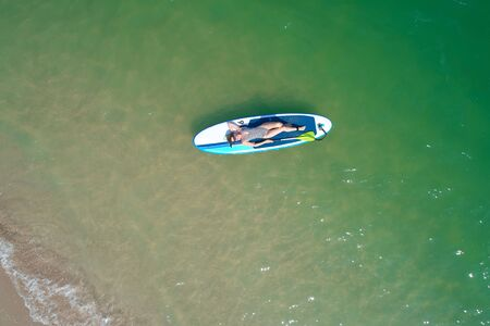 Summer Vacations. Beautiful Young Woman Relaxing on the SUP at Turquoise Water. Beauty, Wellness. Recreation.