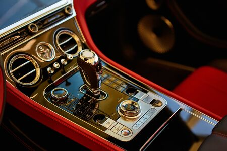 Automatic gear shift handle. Red luxury car Interior. Shallow doff.
