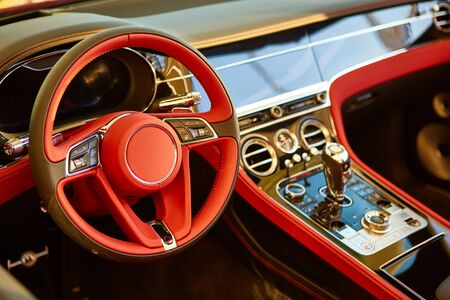 Red luxury car Interior. Steering wheel, shift lever and dashboard. Shallow doff