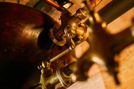 Detalis of medieval traditional distiller cube made from copper production of alcohol, cognac, whiskey. Fragment of copper old distiller for alcohol production. Ancient traditional food technologies for alcohol. Shallow dof Standard-Bild