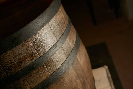wooden barrel on a dark background, in a workshop, in an old room. production of barrels for cognac and wine, in a low key