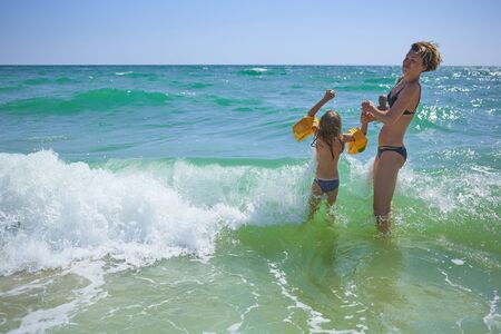 Summer happy family of six years blonde child playing and jumping water waves embracing woman mother in sea shore beach Stockfoto - 133410391