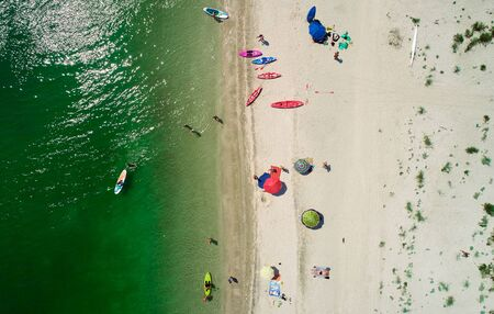 Aerial view of sandy beach with tourists swimming in beautiful sea water.