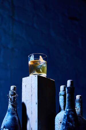 A glass of whiskey with ice on old wooden bar around the old bottles. Shallow dof. The blue tones