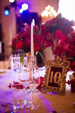 Der Hochzeitsweinlesetisch mit rotem Blumenstrauß.