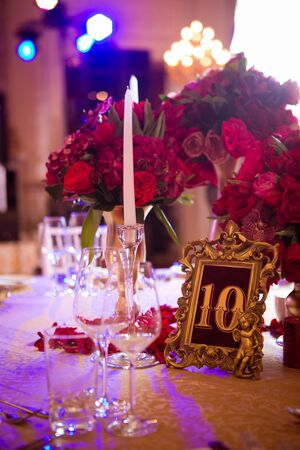 La mesa vintage de boda con ramo rojo.