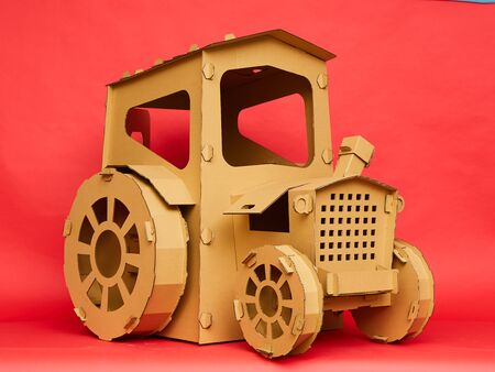 The cardboard tractor on red background. Agricultural and eco concept
