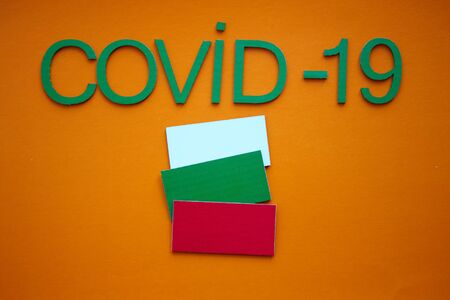 Bulgarian Flag And Inscription COVID-19 made of green cardboard letters, isolated on orange background. World Health Organization WHO introduced new official name for Coronavirus disease named COVID-19. 版權商用圖片