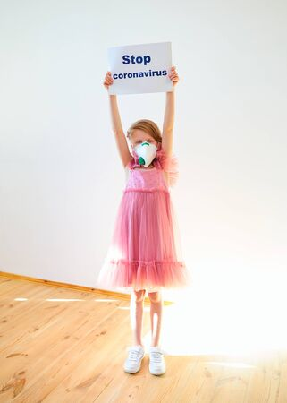 Little girl 7 years old in a medical mask shows banner Stop Coronavirus at home with flecks of sunlight. Concept 2019-nCov. Corona virus outbreaks. Epidemic virus Respiratory Syndrome. Banner for 2019 coronavirus coronavirus concept, pandemic