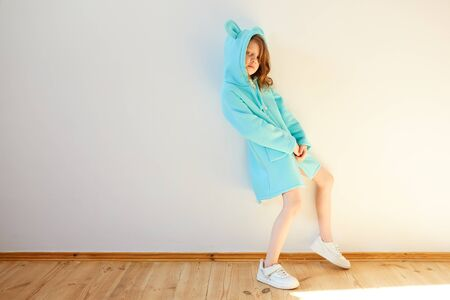 Pretty seven year old girl stands by a white wall and smiling. Kids fashion. Spring style.