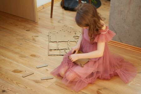A little girl playing with Cardboard Toy Dollhouse Furniture