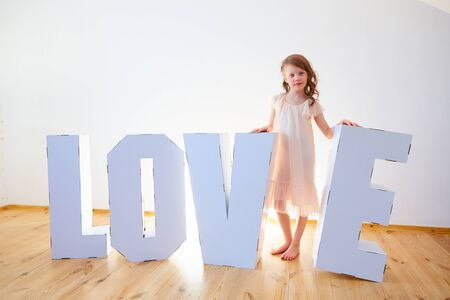 Girl 7 years old playing with big cardboard 3D Standing Letters forming word LOVE from white cardboard on a light background. Relationship concept.