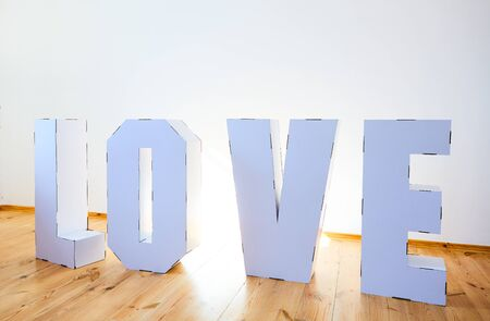 3D Standing Letters forming word LOVE from white cardboard on a light background. Relationship concept.