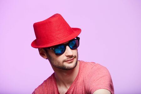 Studio shot of handsome bearded man wearing red fedora hat.