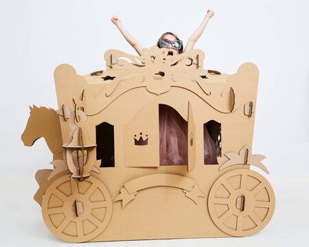 Little princess in crown 7 years old play in carriage made of brown cardboard