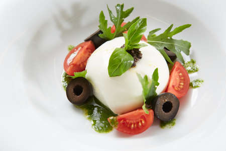 Traditional authentic soft and creamy fresh Italian burrata cheese shaped as white round ball over Italian tomatoes topped with rucola along side pesto reduction