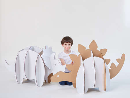 Little dreamer boy playing with a cardboard dinosaurs Triceratops and Stegosaurus. Childhood. Fantasy, imagination.