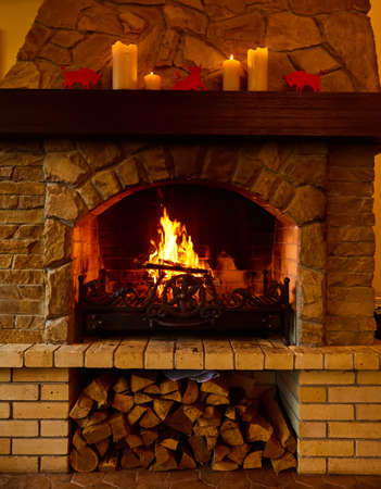 Warm cozy fireplace with real wood burning in it. Cozy winter concept. Christmas and travel background with space for your text.