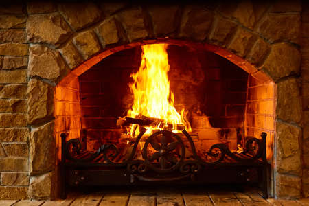 Warm cozy fireplace with real wood burning in it. Cozy winter concept. Christmas and travel background with space for your text. Banco de Imagens