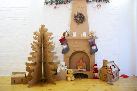 Cardboard Christmas home decoration with tree, gifts and fireplace.