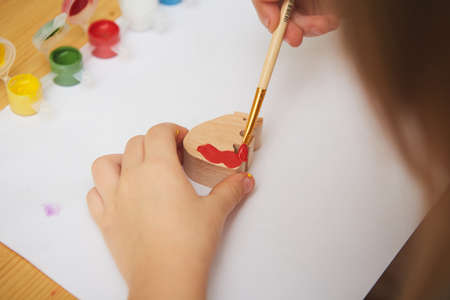 Adorable little girl painting in the room. Idea for DIY indoor activities for children. Shallow dof
