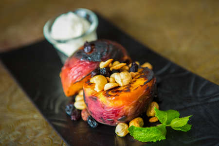 Grilled peaches with nuts and ice-cream. Dessert. Shallow dof.